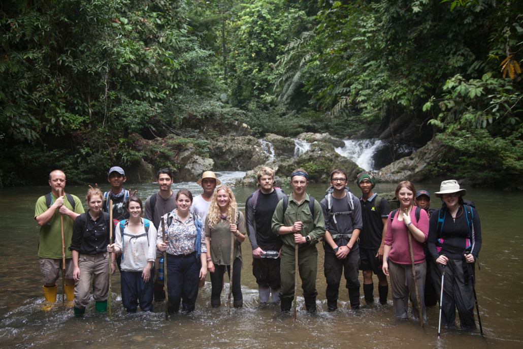 Students from the 2015 field trip pose in front of a waterfall inside the Tane' Olen